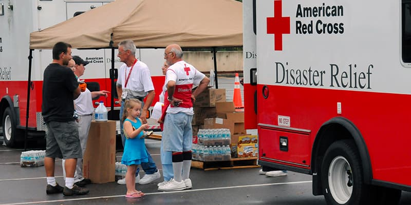 Two American Red Cross volunteers giving aid and relief to a family of three