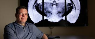 Dr. Grant sitting in front of an MRI image of a brain